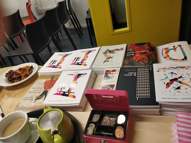 Full colour photo showing what looks like a sales desk covered in piles of books and pamphlets in Verve colours. Also a pink cash box, open, a cup of tea and a green teapot,  some stripey bags, and somebody's dinner on a plate.