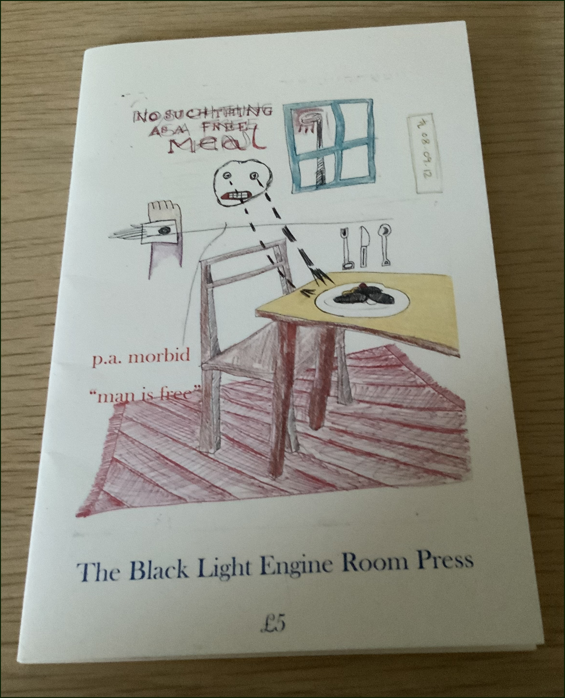 This is a photo of the pamphlet lying on a wooden surface. The jacket is white and most of it's taken up with a colour drawing done roughly, like a doodle really. It's a cartoon. It is a rough drawing of a room with table, chair and window. There's a meal on the table (maybe sausages on the plate), and the cutlery standing up vertically. There is a face with clenched teeth and tears dropping onto the table like two lines of black hyphens. Words above the head in scribbly unclear caps say: THERE'S NO SUCH THING AS A FREE MEAL. The author's name in pink lower case (same colour as the carpet) appears in the middle of the jacket left-justified, with the pamphlet title just below. An inch from the bottom on bold lower case is the title of the press: The Black Light Engine Room Press.