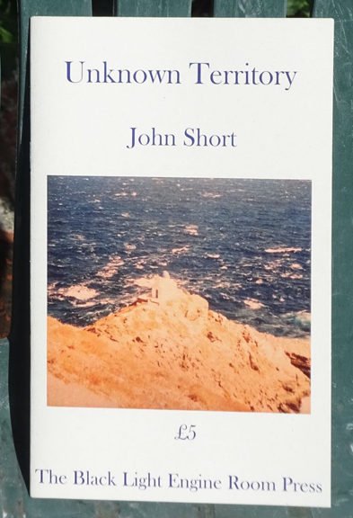 This is a colour photograph of the pamphlet against a green background, maybe a garden chair. It is white, with title and author's name in lower case dark font, centred in the top third. Below this a colour photograph of a spit of soft sand reaching into the sea. Below this the price, centred, and the name of the press.